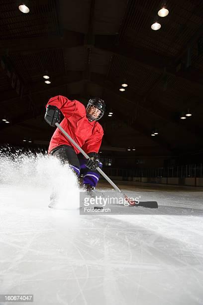 woman hockey player sliding kicking up ice - ice hockey uniform stock pictures, royalty-free photos & images