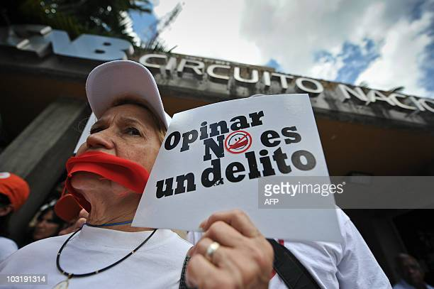 A woman hods a sign reading 'To express ones' opinion is not a crime' as journalists and workers of Venezuelan media demonstrate in support of 32...