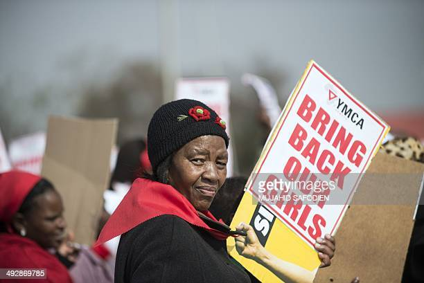 A woman hold a placard as hundreds of Soweto residents march at the YMCA in Soweto Johannesbourg on May 22 to demonstrate for the release of more...