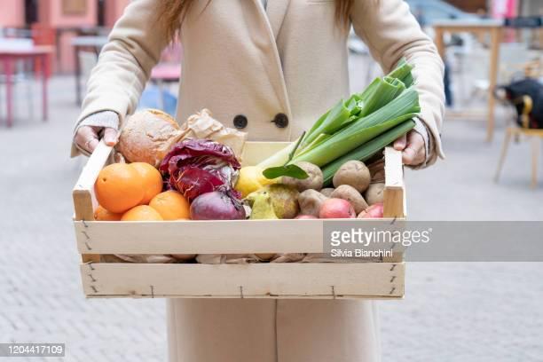 woman hold a wooden box with fresh organic vegetables - consegna a domicilio foto e immagini stock