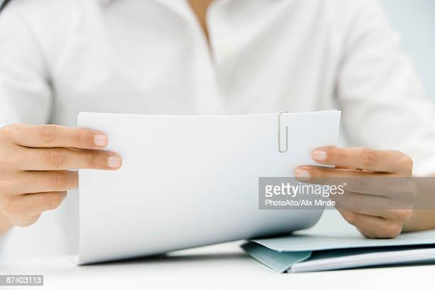 Woman hold document bound with paperclip, cropped view