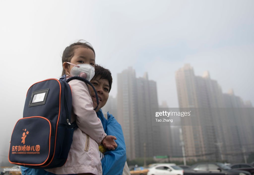 A woman hold her child with mask at the Changjiang street during dense fog enveloping Harbin on September 14, 2018 in Harbin, China. The meteorological department issued a yellow alert for dense fog