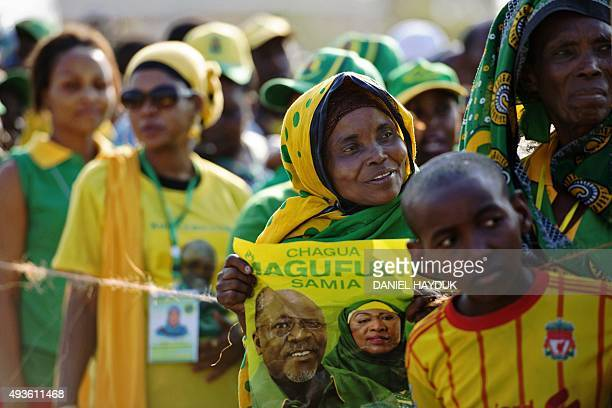A woman hold leans over to get a glimpse of presidential candidate John Magufuli as she holds a poster of him during a ruling Chama Cha Mapinduzi...