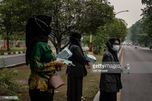 Woman hold masks as they prepare to distributions mask to motorcyclist as haze from the forest fires blanket the area in Palangkaraya city on...