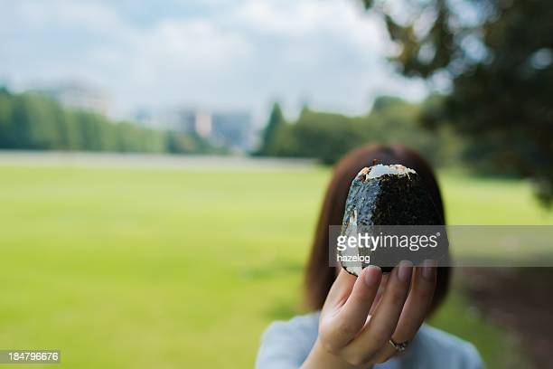 woman hold out a riceball - rice ball stock pictures, royalty-free photos & images