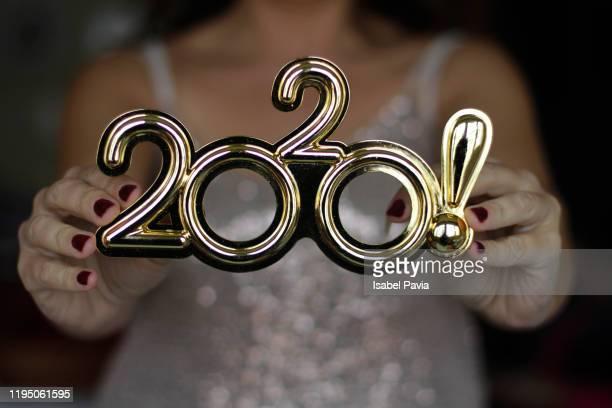 woman holding 2020 eyeglasses. new year's eve concept - nieuwjaarsreceptie stockfoto's en -beelden