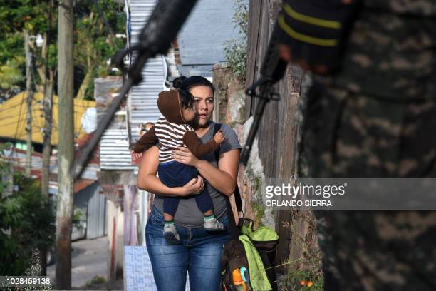 TOPSHOT A woman holding a baby looks at soldiers and military police during an operation in search of gang members in Tegucigalpa on September 7 2018...