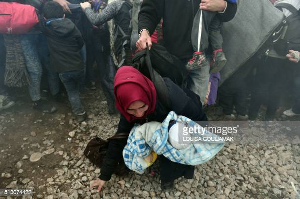 Woman holding a baby runs away with other migrants and refugees after Macedonian police fired tear gas at hundreds of Iraqi and Syrian migrants who...