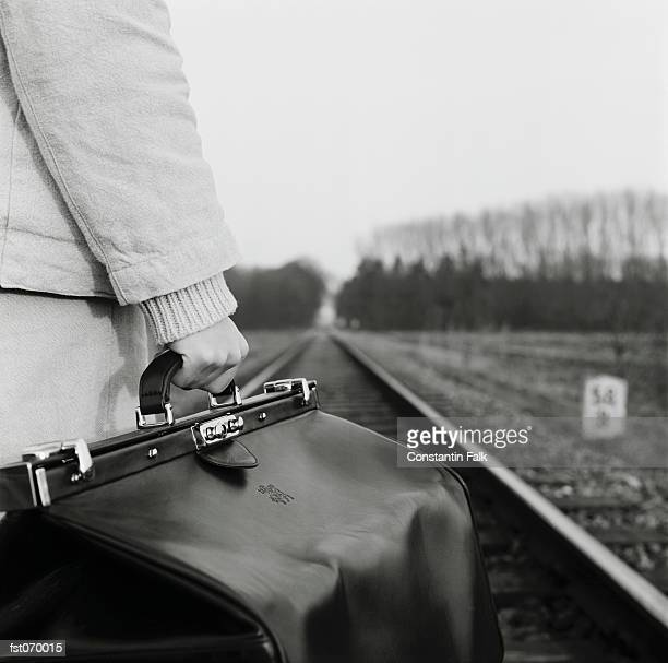 A woman holding a bag on train tracks