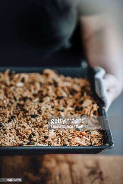 woman holding a baking tray with freshly baked homemade granola. healthy vegan snack. - granola stock pictures, royalty-free photos & images