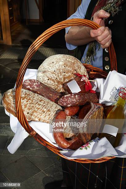 a woman holding a basket of sausages and bread, focus on basket, carinthia, austria - gerookte worst stockfoto's en -beelden