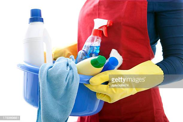 woman holding a basket with cleaning materials