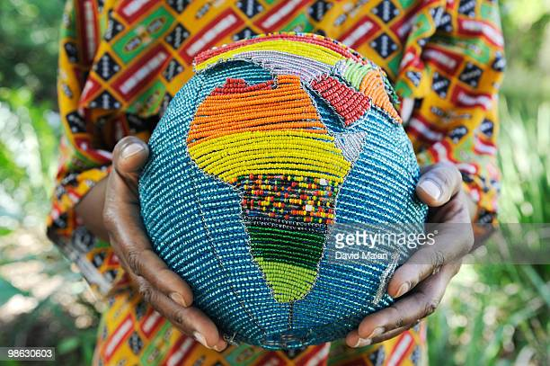 Woman holding a beaded globe with africa showing