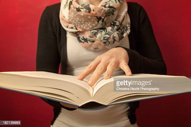 woman holding a big old book - christina grosse stock-fotos und bilder