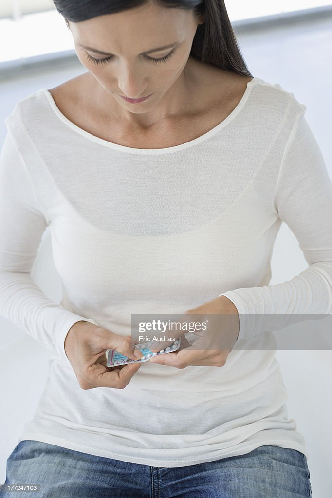 Woman holding a blister pack of contraceptive pills : Stock Photo