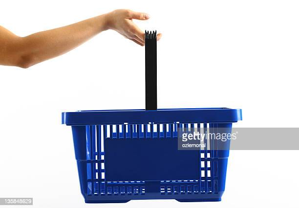 a woman holding a blue shopping basket - basket stock photos and pictures