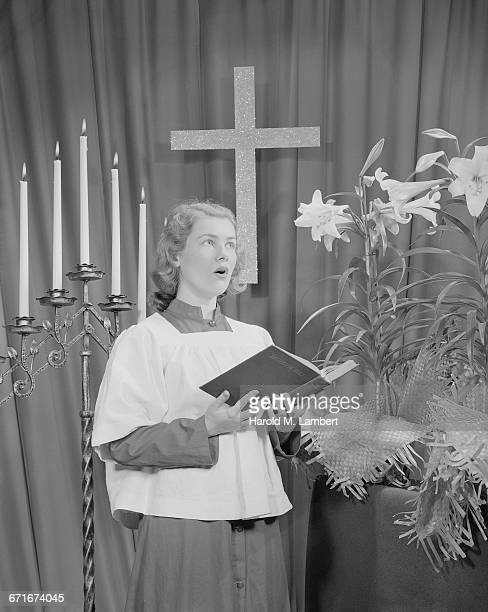 woman holding a book and singing during christmas celebration - {{relatedsearchurl(carousel.phrase)}} imagens e fotografias de stock