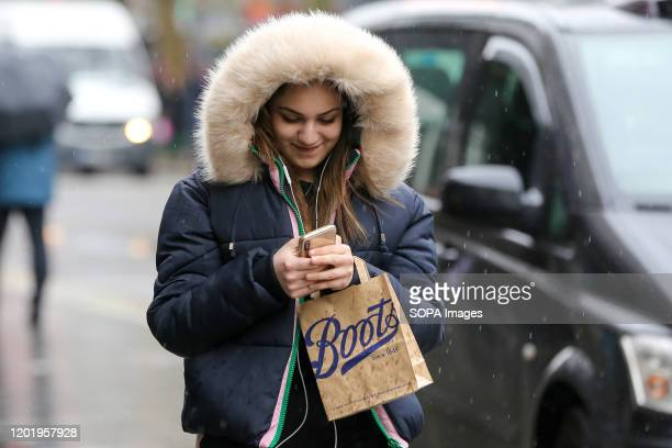 Woman holding a Boots' shopping bag walks in central London while using her mobile phone.