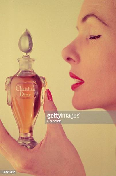 Woman holding a bottle of Miss Dior perfume by Christian Dior, December 1954. The half ounce flagon is presented in a Baccarat crystal bottle, and...