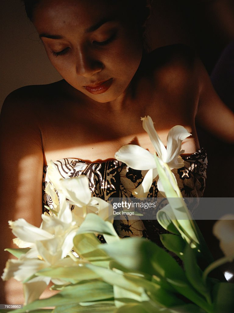 Woman holding a bouquet lily flowers, eyes closed : Stock Photo