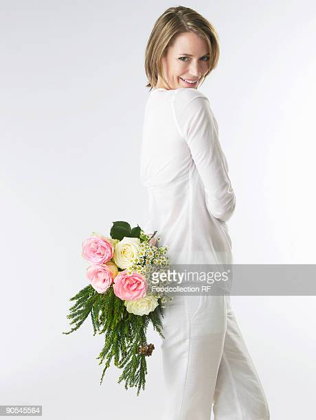 woman holding a bouquet of flowers behind her back, smiling - 若い女性一人 ストックフォトと画像