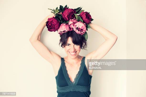 Woman holding a bouquet of flowers on her head