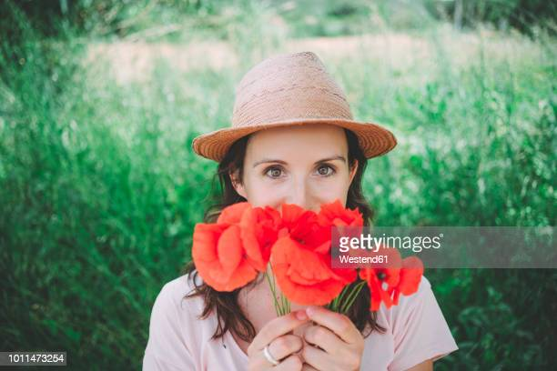 woman holding a bouquet of red poppies in spring - red hat stock pictures, royalty-free photos & images