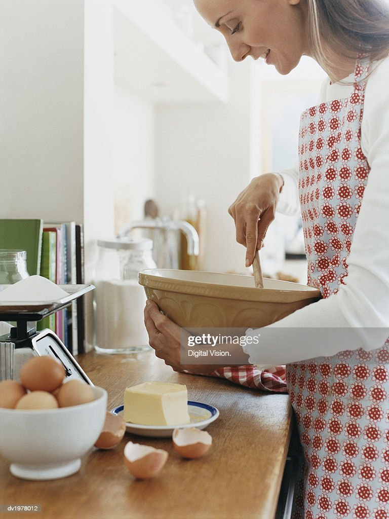 Woman Holding a Bowl and a Wooden Spoon in a Kitchen : Stock Photo