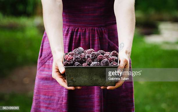 Woman holding a bowl of blackberries