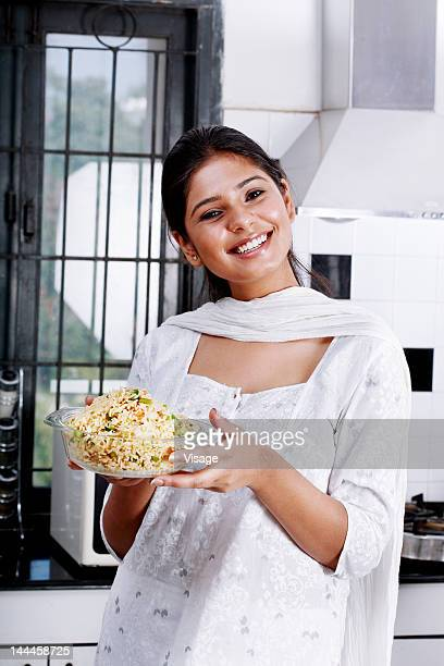 Woman holding a bowl of vegetable rice
