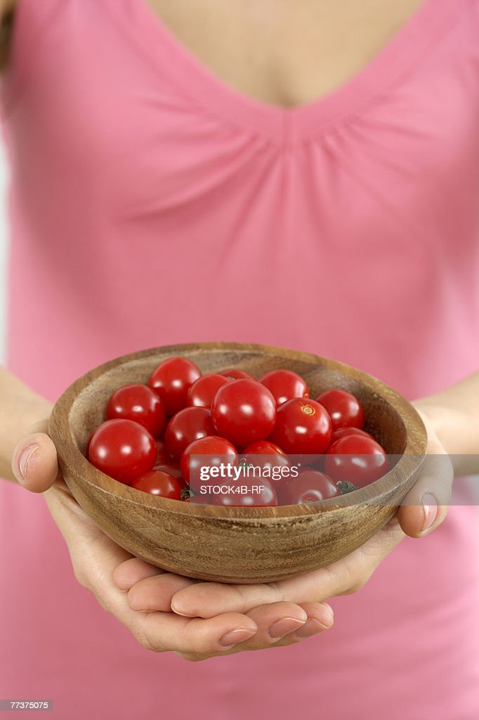 Woman holding a bowl with cherry tomatoes : Photo