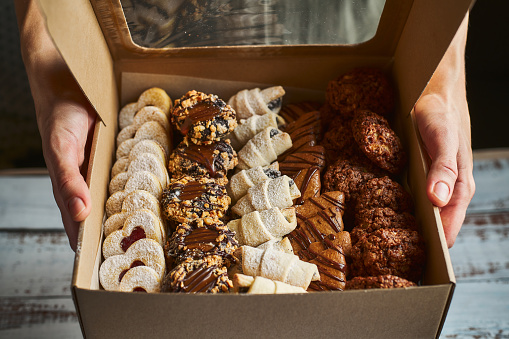 Woman holding a box filled with mini Christmas pastry cakes 1184180166