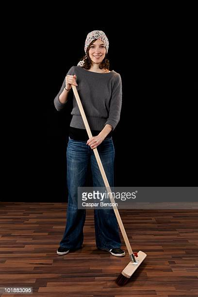 A Woman Holding A Broom