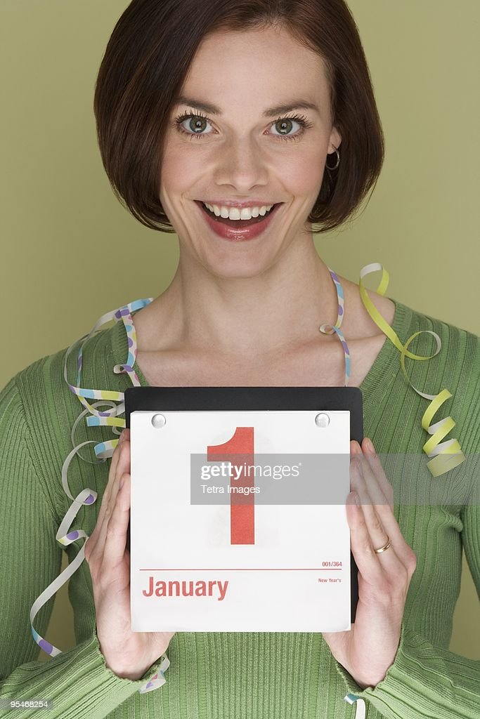 Woman holding a calendar on January first : Stock Photo