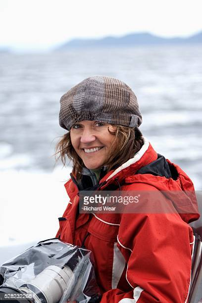 a woman holding a camera wrapped in plastic on a cruise ship tour - photojournalist stock pictures, royalty-free photos & images
