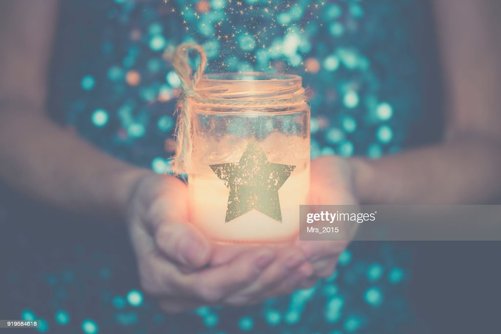 Woman holding a candle in her hands : Stock Photo