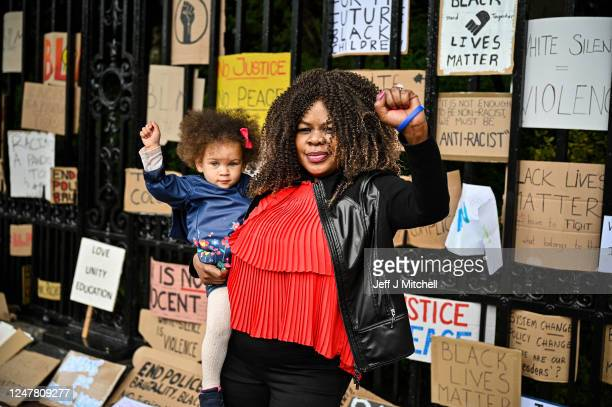 Woman holding a child, raise their fists in the air as Black Lives Matter protesters hang their banners on the fence of Holyrood Palace, despite a...
