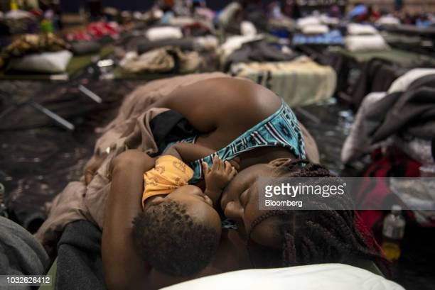 A woman holding a child sleeps after being evacuated at Southeast Raleigh High School ahead of Hurricane Florence in Raleigh North Carolina US on...