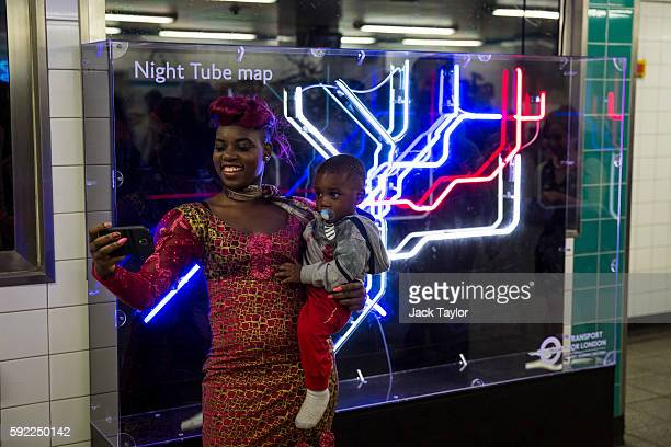A woman holding a child takes a selfie in front of a neon installation of the Night Tube map in Brixton Underground Station on August 19 2016 in...