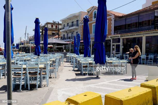 A woman holding a child walks past closed shops and restaurants on the Greek island of Lesvos on May 3 2018 as professional and trade organizations...