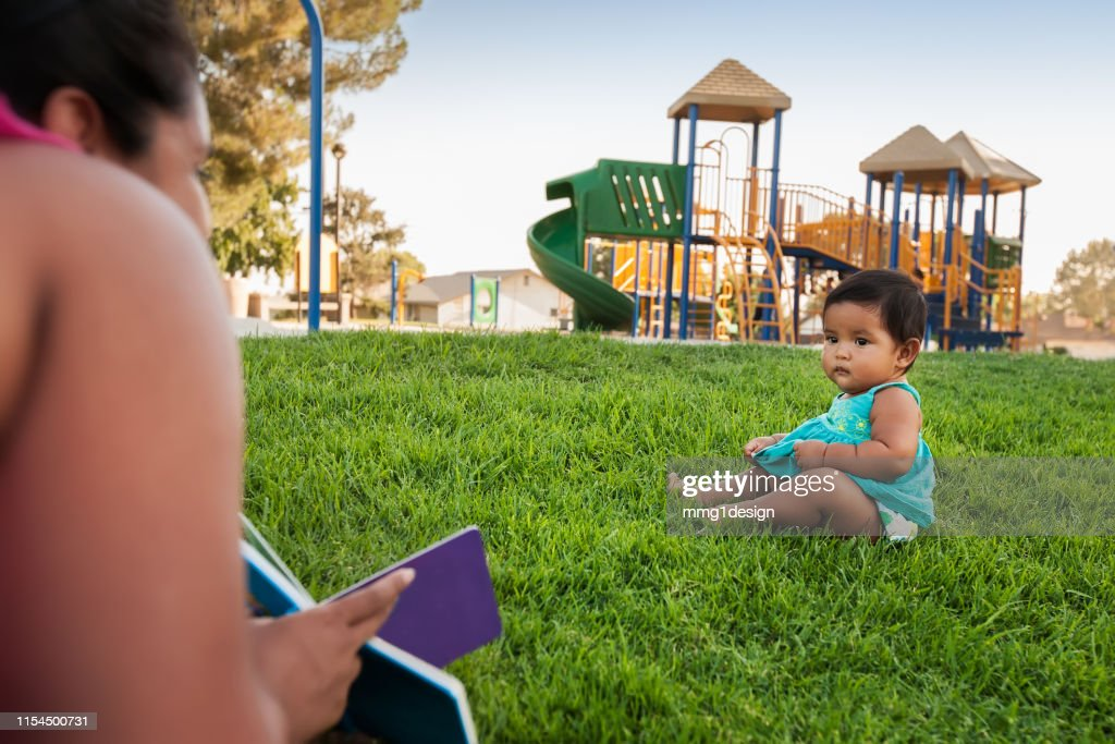 A woman holding a childrens book tries to engage the attention of a baby girl sitting in the lawn of a kids playground. : Stock Photo