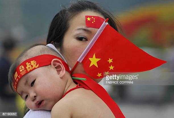 A woman holding a Chinese flag carries a baby in Tiananmen square in Beijing on August 6 2008 two days before the opening of the 2008 Beijing...