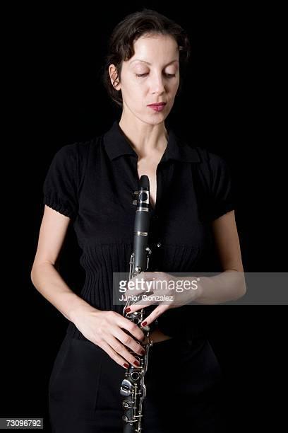 woman holding a clarinet - clarinetto foto e immagini stock