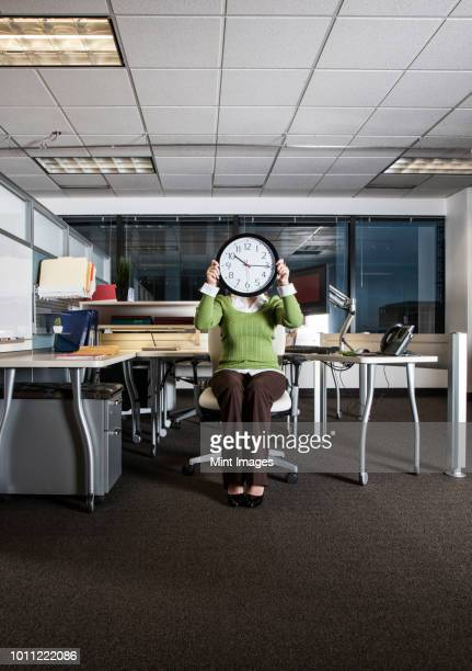 Woman holding a clock face while sitting in her cubicle office space.
