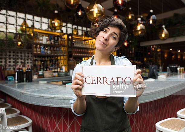 Woman holding a closed sign in Spanish at a restaurant