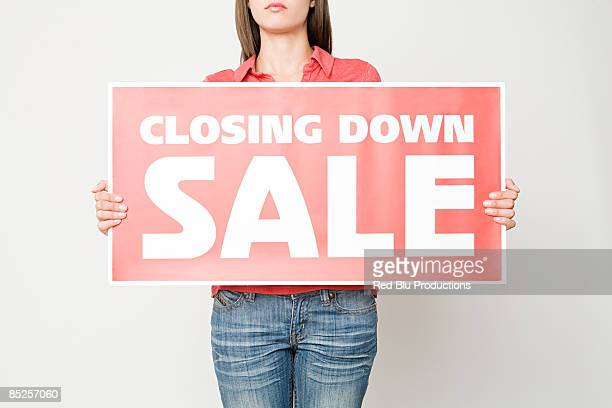 Woman holding a closing down sign