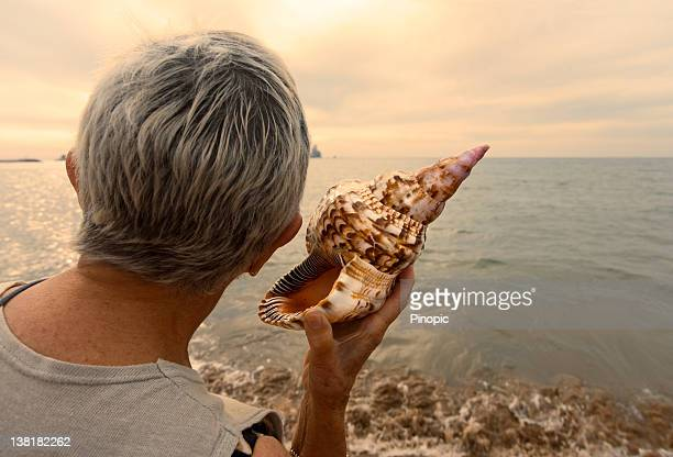 woman holding a conch as listening the sea - conch shell stock pictures, royalty-free photos & images