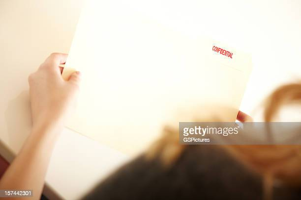 Woman Holding a Confidential folder of documents