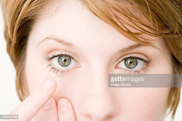 a woman holding a contact lens - contacts stock photos and pictures