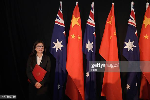 A woman holding a copy of the Free Trade Agreement stands next to National flags of China and Australia during a signing ceremony on June 17 2015 in...